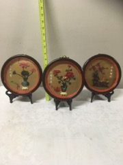 Three chinese home decor items on stands